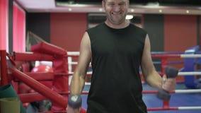 L'uomo scuote i suoi muscoli nella palestra con l'aiuto delle teste di legno video d archivio