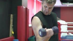 L'uomo scuote i suoi muscoli nella palestra con l'aiuto delle teste di legno archivi video