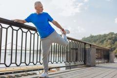 L'uomo senior che allunga la gamba muscles prima del funzionamento di mattina Fotografia Stock Libera da Diritti