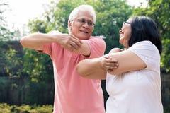 L'uomo senior che assiste la sua moglie durante scaldarsi esercita il outdoo fotografia stock