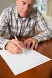 L'uomo senior che firma l'ultima volta e testamento a casa Fotografia Stock