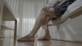 L'uomo senior che si fa terapia di massaggio sulle sue gambe stanche allevia il dolore e sollecita a casa - video d archivio