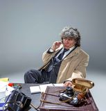 L'uomo senior come l'agente investigativo o capo della mafia sul fondo grigio dello studio Fotografie Stock Libere da Diritti