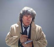 L'uomo senior come l'agente investigativo o capo della mafia sul fondo grigio dello studio Fotografia Stock
