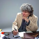 L'uomo senior come l'agente investigativo o capo della mafia sul fondo grigio dello studio Immagini Stock