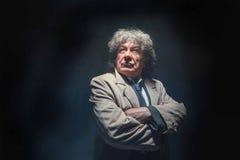 L'uomo senior come l'agente investigativo o capo della mafia sul fondo grigio dello studio Immagine Stock