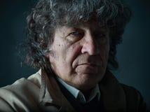 L'uomo senior come l'agente investigativo o capo della mafia sul fondo grigio dello studio Fotografie Stock