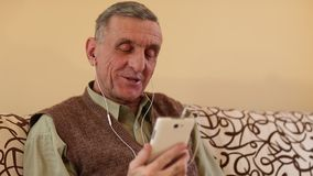 L'uomo senior comunica tramite uno smartphone Uomo con il telefono cellulare archivi video