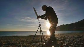 L'uomo senior dipinge un'immagine sulla spiaggia L'artista maschio anziano dipinge la condizione contro l'innalzamento del sole s video d archivio