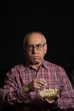 L'uomo senior guarda la TV Immagini Stock