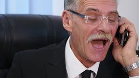 L'uomo senior parla con lo smartphone bianco in ufficio Fine in su stock footage