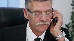 L'uomo senior parla con lo smartphone bianco in ufficio Fine in su archivi video