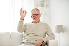 L'uomo senior sorridente che mostra la mano giusta firma a casa Immagine Stock