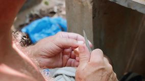 L'uomo senior taglia il sughero per fare una flauto del lavoro manuale, primo piano stock footage