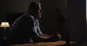 L'uomo senior turbato è solo con la bottiglia della birra nella stanza scura archivi video