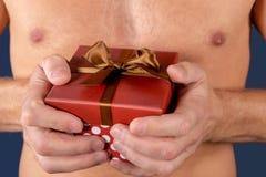 L'uomo senza camicia giudica un contenitore di regalo isolato su bianco sorpresa Colpo dello studio Festa ed occasione speciale immagine stock