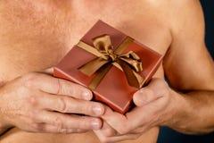 L'uomo senza camicia giudica un contenitore di regalo isolato su bianco sorpresa Colpo dello studio Festa ed occasione speciale immagini stock libere da diritti