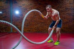 L'uomo senza camicia muscolare in una palestra si esercita con le corde di battaglia durante il suo addestramento ad alta intensi Fotografia Stock