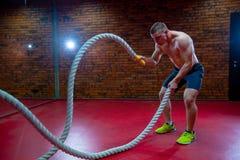 L'uomo senza camicia muscolare in una palestra si esercita con le corde di battaglia durante il suo addestramento ad alta intensi Immagini Stock Libere da Diritti