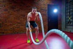 L'uomo senza camicia muscolare in una palestra si esercita con le corde di battaglia durante il suo addestramento ad alta intensi Fotografia Stock Libera da Diritti