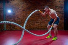 L'uomo senza camicia muscolare in una palestra si esercita con le corde di battaglia durante il suo addestramento ad alta intensi Fotografie Stock Libere da Diritti