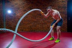 L'uomo senza camicia muscolare in una palestra si esercita con le corde di battaglia durante il suo addestramento ad alta intensi Immagine Stock Libera da Diritti