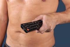 L'uomo senza camicia tiene il telecomando a disposizione, isolato sopra fondo blu fotografia stock libera da diritti