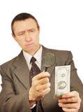 L'uomo serio guarda tramite una lente d'ingrandimento sul dollaro Immagini Stock