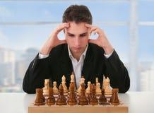 L'uomo serio pensa sul gioco di scacchi Fotografia Stock