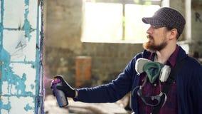 L'uomo serio sta dipingendo i graffiti sulla colonna sporca in vecchia casa vuota con la pittura dell'aerosol Il tipo sta indossa archivi video
