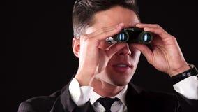 L'uomo serio sta guardando intorno in binocolo archivi video