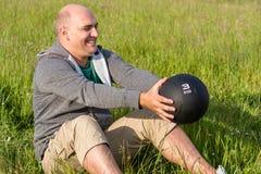L'uomo si prepara con una palla medica da 3 chilogrammi che si siede sui gras Fotografie Stock