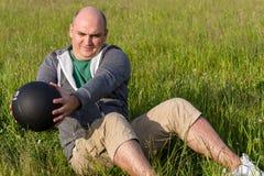 L'uomo si prepara con una palla medica da 3 chilogrammi che si siede sui gras Immagini Stock