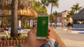 L'uomo si rilassa su sunbath nella piscina con per mezzo del telefono cellulare video d archivio