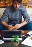 L'uomo si siede ad una tavola nel posto di lavoro Immagini Stock