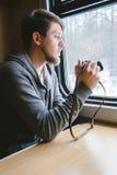 L'uomo si siede ad una tavola in un treno con una macchina fotografica Fotografia Stock Libera da Diritti