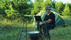 L'uomo si siede alla tenda, guardante il vaso appendere sopra il fuoco e funzionare con il computer portatile stock footage