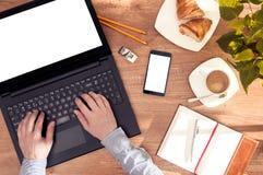 L'uomo si siede allo scrittorio con il computer portatile e lo smartphone Immagine Stock Libera da Diritti