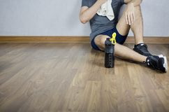 L'uomo si siede e riposa dopo l'allenamento, con la bottiglia dello sport acquatico immagini stock