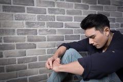 L'uomo si siede e ritiene depresso Fotografia Stock Libera da Diritti