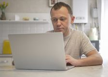 L'uomo si siede nella sua cucina con un computer portatile fotografia stock libera da diritti