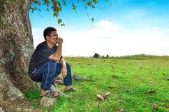 L'uomo si siede sotto l'albero Fotografia Stock Libera da Diritti