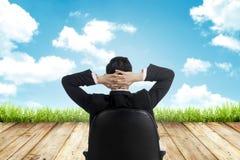 L'uomo si siede sulla sedia che guarda il cielo Fotografia Stock Libera da Diritti