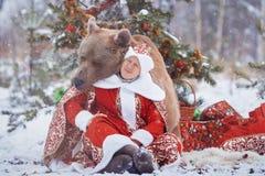 L'uomo si siede vicino all'orso bruno immagine stock libera da diritti