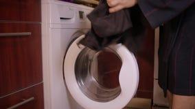 L'uomo si sporca i vestiti dalla lavatrice stock footage