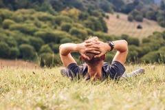 L'uomo si trova in alta erba verde Fotografia Stock Libera da Diritti