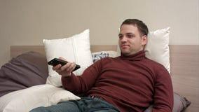 L'uomo si trova a letto guarda la televisione e sorridere Immagine Stock