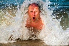 l'uomo si tuffa le onde con schiuma sorpreso respira l'aria attraverso la sua bocca immagini stock