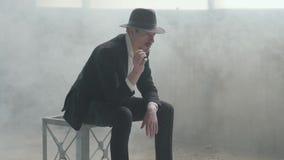 L'uomo sicuro bello del ritratto in un cappello getta su e prende la moneta che si siede in una costruzione abbandonata La testa  archivi video