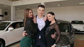L'uomo sicuro di sé con due ragazze nella sala d'esposizione sceglie una nuova automobile video d archivio